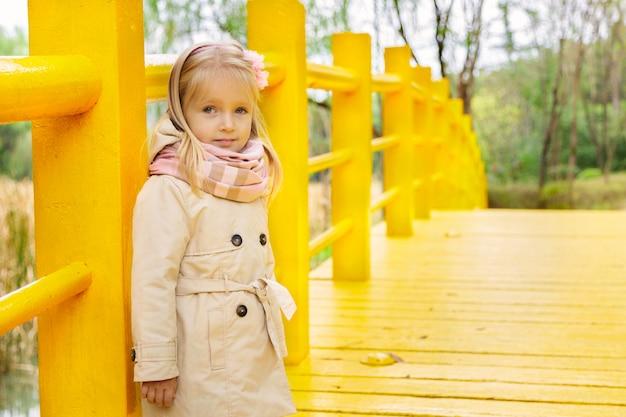 Stylish llittle girl on a yellow bridge in the park
