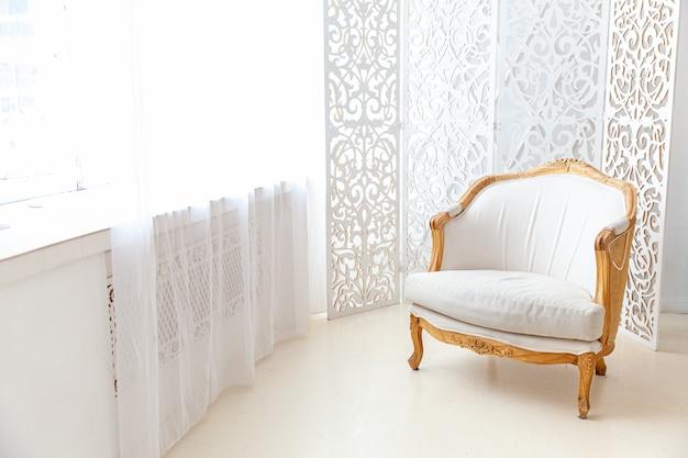 スタイリッシュなロフトベッドルームのインテリア。明るい壁の大きな窓とアームチェアを備えた広々としたデザインのアパートメントです。ミニマリストのスカンジナビアスタイルのエレガントな家具を備えた清潔でモダンな装飾。