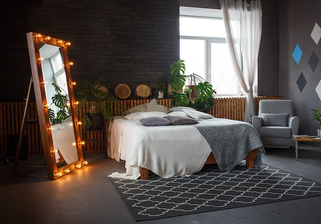 Stylish loft cozy living room with double bed, armchair