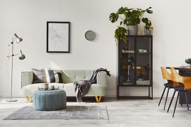 Стильный интерьер в стиле лофт с зеленым диваном, дизайнерской отделкой пуфами и элегантными аксессуарами. современный домашний декор.