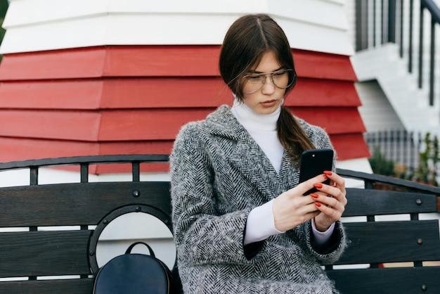 Стильная длинноволосая девушка-модель в синем свитере сидит на детской площадке в лучах утреннего солнца