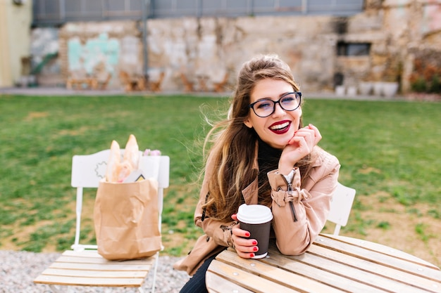 Stylish long-haired girl wearing brown coat and glasses, drinks latte in cafe after shopping with bags on chair behind. coffee break in outdoor restaraunt on the blur background.