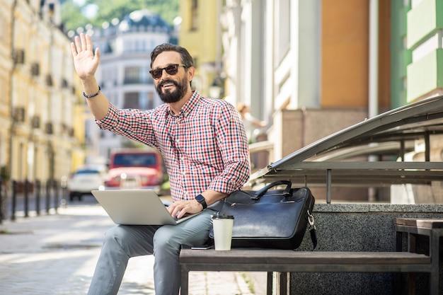 スタイリッシュな外観。通りすがりの人に挨拶しながら屋外に座っている前向きなひげを生やした男