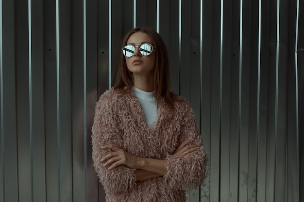 Stylish look up fashion tall model long brown hair woman in sunglasses with mirror effect in pink coat and white shirt poses laying with hands crossed on industrial storage parking metallic background