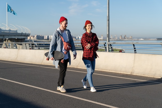 Stylish lovers couple or friends walk outdoors talking trendy hipsters with skateboard on bridge