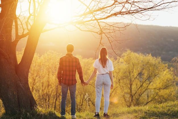 スタイリッシュな恋人たちが手をつないで立って、大きな木の下で素晴らしい夕日を眺めています。