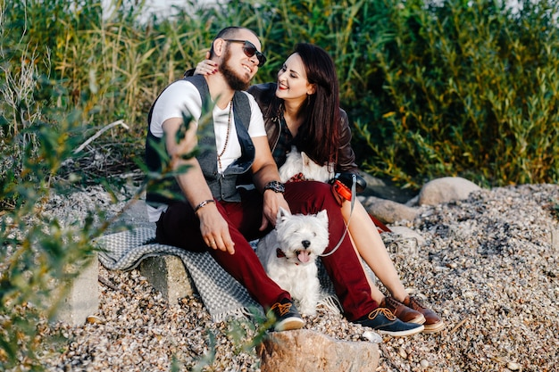 Stylish loving couple sitting on the seashore together with white dogs