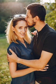 Stylish loving couple standing in a park.
