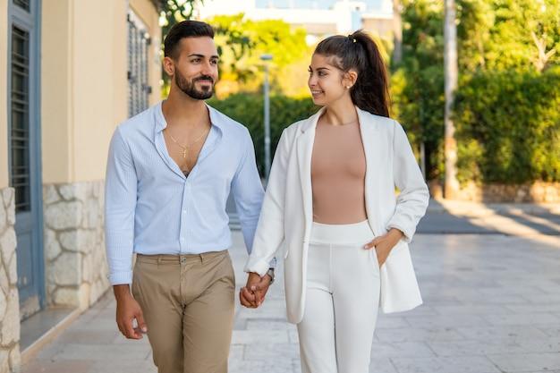 Stylish loving ethnic couple walking together in city