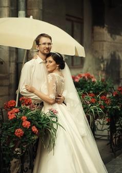 Стильная роскошная невеста и элегантный жених, нежно обнимающиеся на фоне старого города львова.