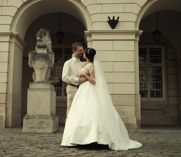 Стильная роскошная невеста и элегантный жених, нежно обнимающиеся на улице старого города львова.