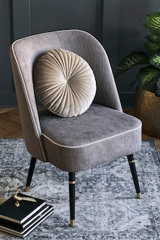 Stylish and luxury composition of design gray armchair with books, sculpture, plant in gold pot and elegant accessories. interior design. modern home staging. close up.