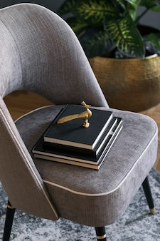 Stylish and luxury composition of design gray armchair with books template modern home staging