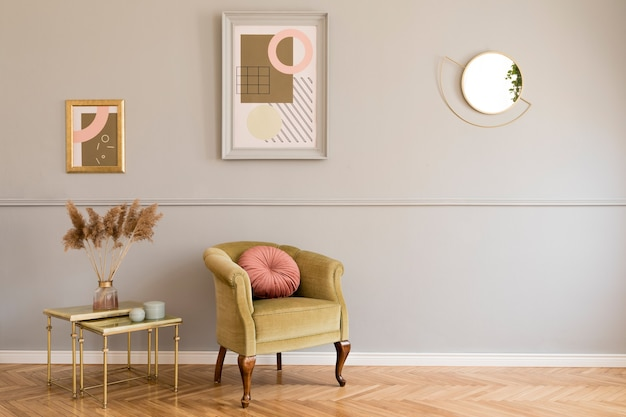 Stylish and luxury living room interior with elegant green armchair, retro tables, design lamps, chic accessories, gold mirror and mock up frames on the molding gray wall. template.