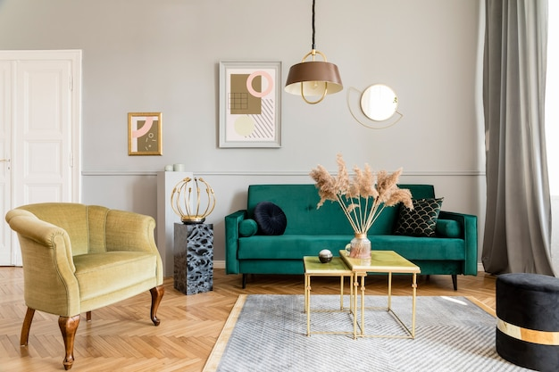 Stylish and luxury living room interior with elegant green velvet armchair, sofa, coffee table, marble stands, design lamps, art paintings and chic accessories in home decor.