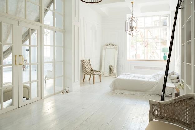 Стильный дизайн интерьера роскошной белой спальни в мягком дневном свете с элегантной классической мебелью