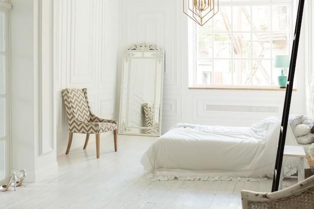 エレガントでクラシックな家具を備えた柔らかな日の光の中でスタイリッシュで豪華な白い寝室のインテリアデザイン