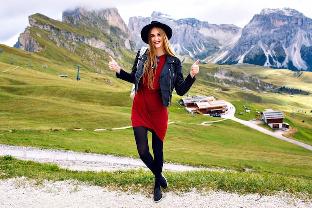 Elegante donna magnifica con i capelli lunghi, che indossa cappello alla moda, mini abito e giacca di pelle sulle alpi