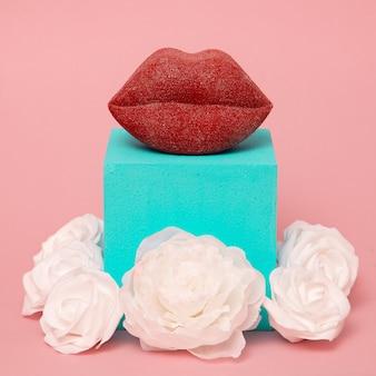 スタイリッシュなメイクアップコンポジションの唇と白いバラ。ミニマルアート