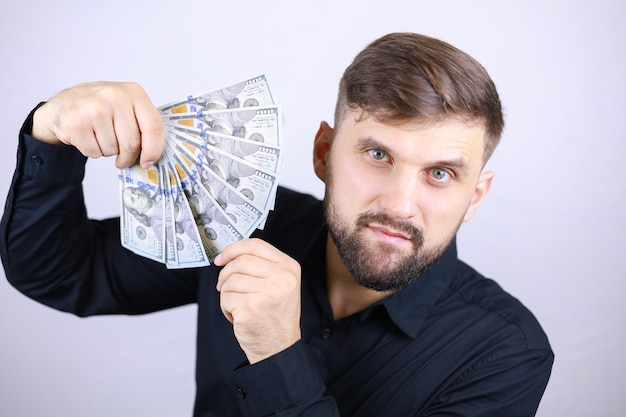 Stylish male businessman in a black shirt holding money in his hands