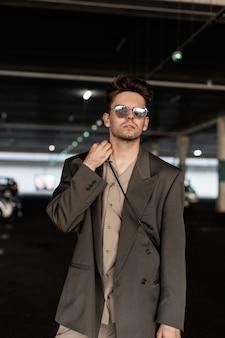 ファッションブレザーとシャツのサングラスと駐車場を歩くスタイリッシュな男性実業家モデル