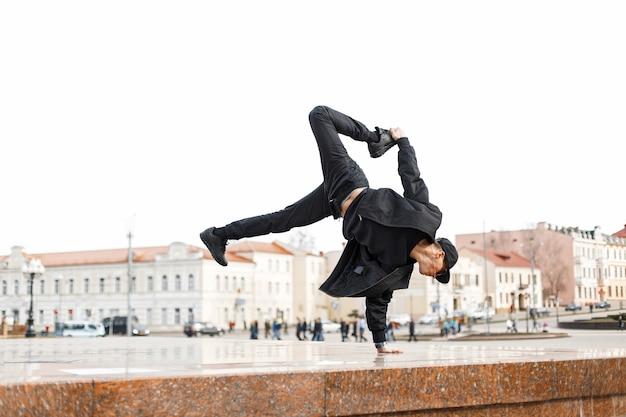 Стильный танцор в черных очках и кепке танцует на улице