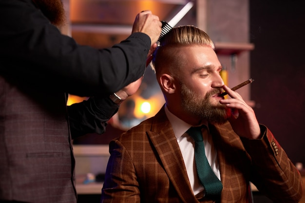 Stylish male enjoy haircut at the hairdresser, he is smoking during process of cutting
