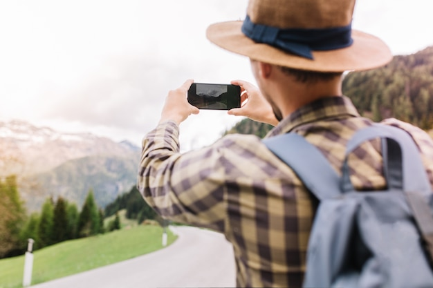 Stylish male traveler exploring italy and taking picture of beautiful nature views holding his smartphone