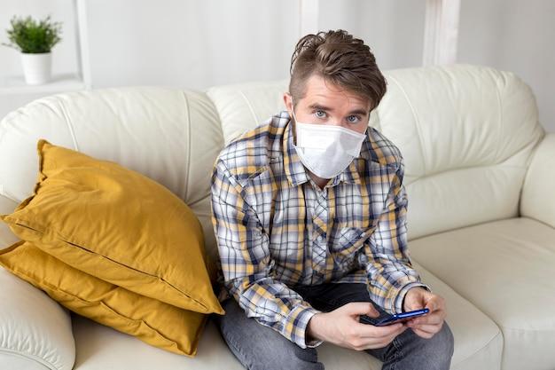 Стильный мужчина с маской для лица позирует на диване