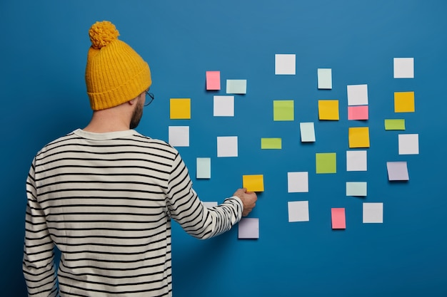 Stylish male youngster in fashionable outfit stands back to camera, turns to blue wall, sticks small colorful notes for putting down main ideas