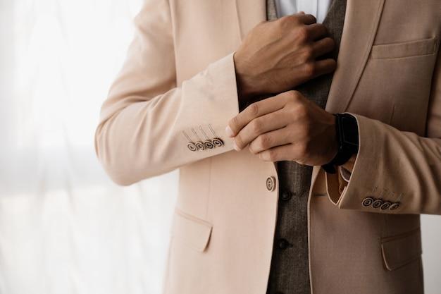 スタイリッシュな男は彼のジャケットの袖を調整します