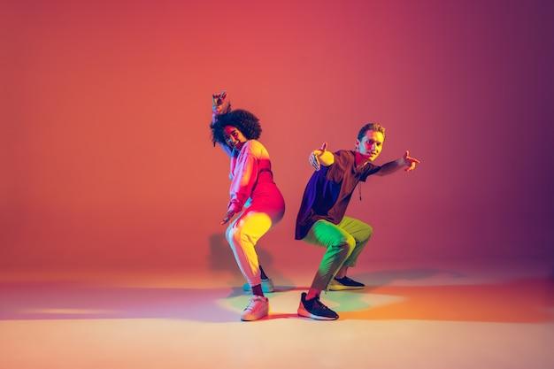 Стильный мужчина и женщина танцуют хип-хоп в яркой одежде на зеленом фоне в танцевальном зале в неоновых тонах