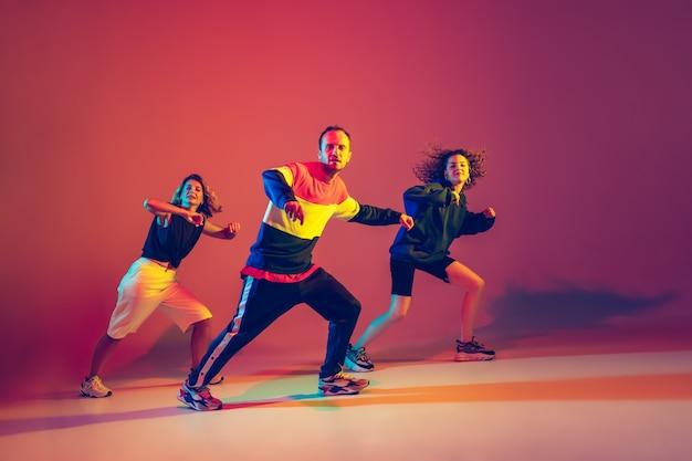 Стильные мужчины и женщины танцуют хип-хоп в яркой одежде на градиентном фоне