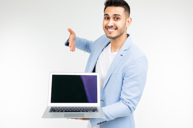 Stylish man in a blue jacket shows a laptop display with a blank template for inserting a site on a white studio background