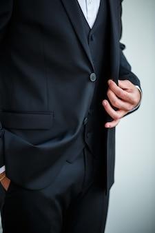 黒のジャケットのボタンをボタンで留めるスタイリッシュな男性実業家