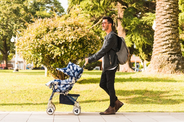 Stylish man carrying backpack walking with baby stroller in the park