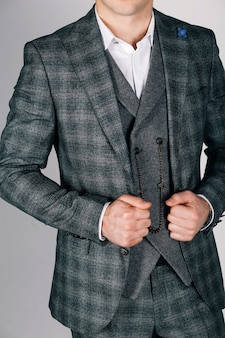 Stylish man in checkered suit on gray