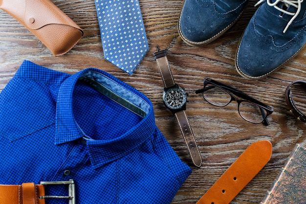 Stylish man clothing and accessories flat lay in blue and brown colors on a wooden table