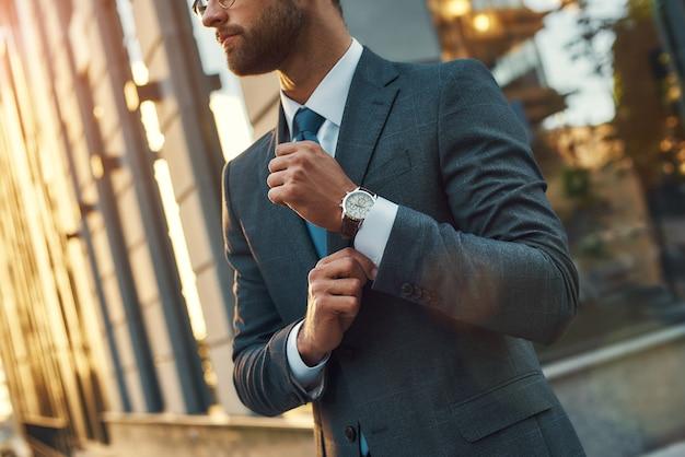 屋外に立っている間彼の袖を調整するフルスーツのスタイリッシュな男自信の実業家