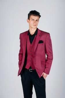 Stylish man in a crimson jacket on grey