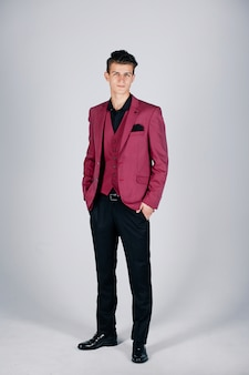 Stylish man in a crimson jacket on a light background