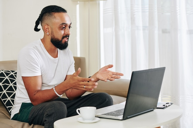 Stylish man drinking coffee and video calling friends or coworkers
