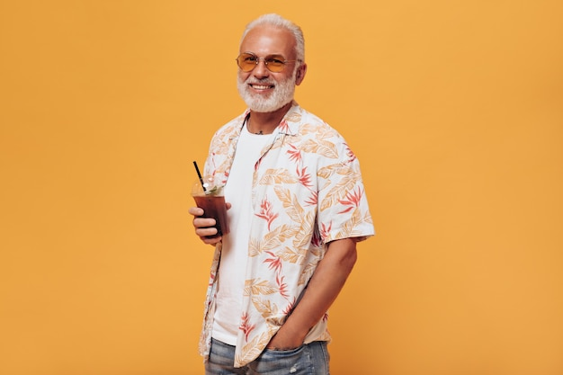 Stylish man in eyeglasses holds cocktail to go on orange wall