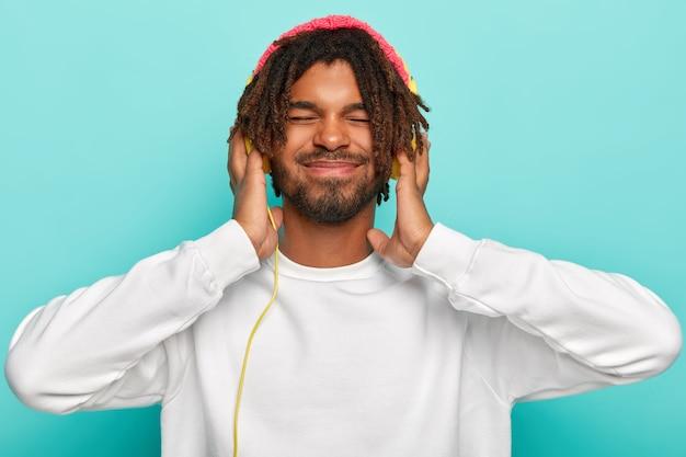 Stylish man focused on song, keeps both hands on modern headphones, enjoys loud sound, keeps eyes closed from pleasure, wears white casual jumper