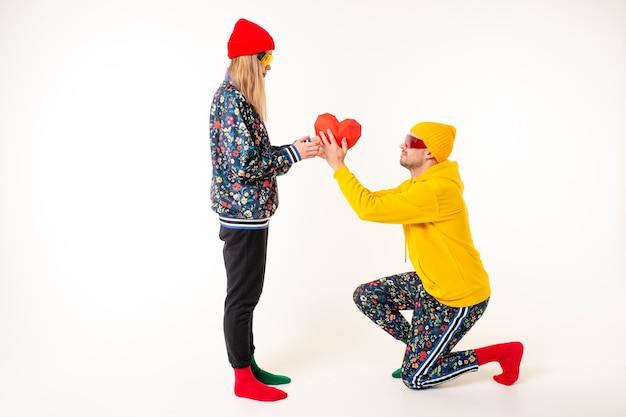 흰 벽 위에 화려한 옷을 입고 여자 친구에게 마음을 선물하는 세련된 남자 프리미엄 사진