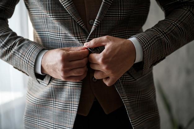 彼のジャケットのボタンをボタンで留めるスタイリッシュな男の新郎