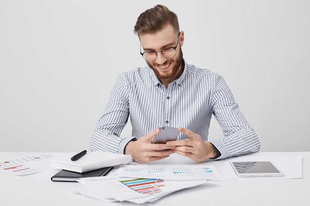 Stylish man has trendy hairdo types messages on smart phone