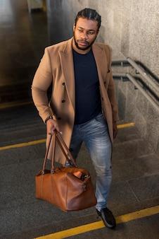 革のバッグを保持しているスタイリッシュな男