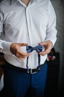 Stylish man holding a butterfly close-up. fashion.