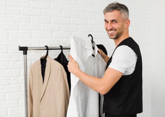 Stylish man holding clothes and smiles